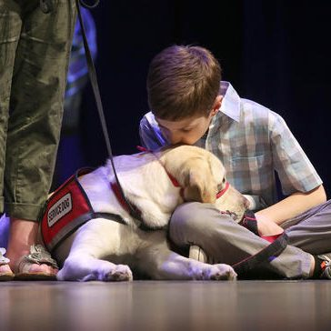 (042918 Fitchburg, MA) Derek Blake, 9 1/2 kisses his social dog Jean during NEADS service dog graduation ceremony in Fitchburg on Sunday,April 29, 2018. Staff Photo by Nancy Lane
